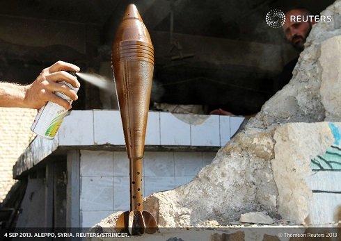 Egy szír lázadó festékkel szórja le az aknavető burkolatát