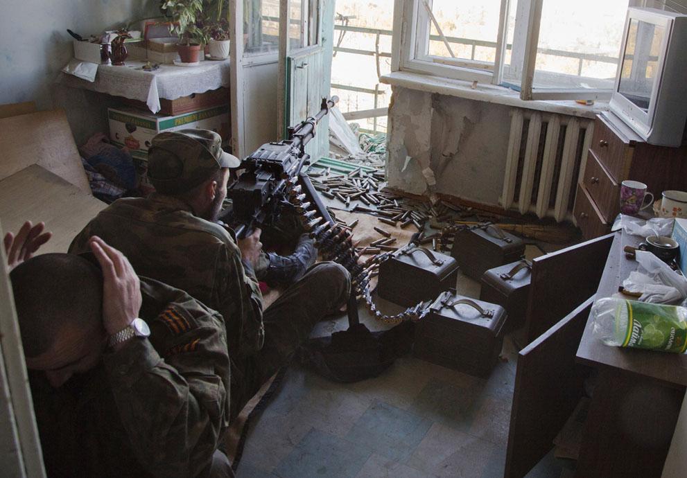 Oroszbarát lázadók géppuskázzák ukrán állásokat a repülőtér közelében.  (AP Fotó / Dmitry Lovetsky)