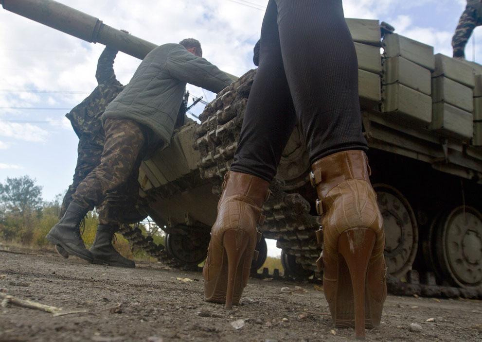 Egy nő előtt áll egy ukrán tank előtt egy ellenőrzőpont közelében Mayorovonál, Donyeckben. (Anatolii Boiko / AFP)