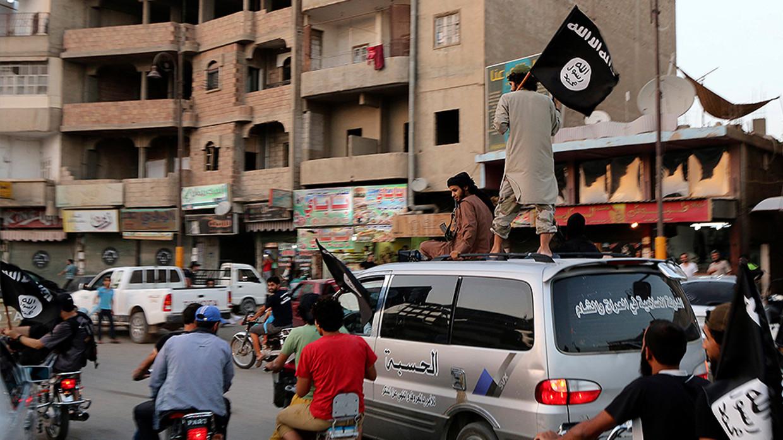 Az IS-hez hű tagok az IS-zászlókat lengetik, amikor körbejárják a szír Rakkát© Reuters