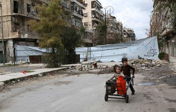 Gyermekek eltolni egy szekeret vízzel konténerek mentén sérült utcán a régi Aleppo március 11-én.