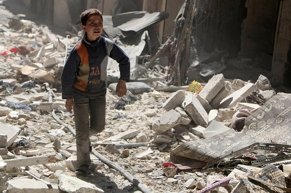 A boy walks on rubble of damaged buildings at a site hit by what activists said was an airstrike by forces loyal to Syria's President Bashar al-Assad in Aleppo's district of al-Sukari on March 23